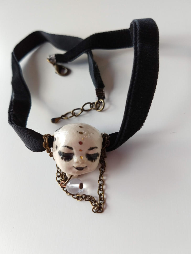 necklace with a sleeping face on a velvet ribbon by ursula aavasalu tigukass
