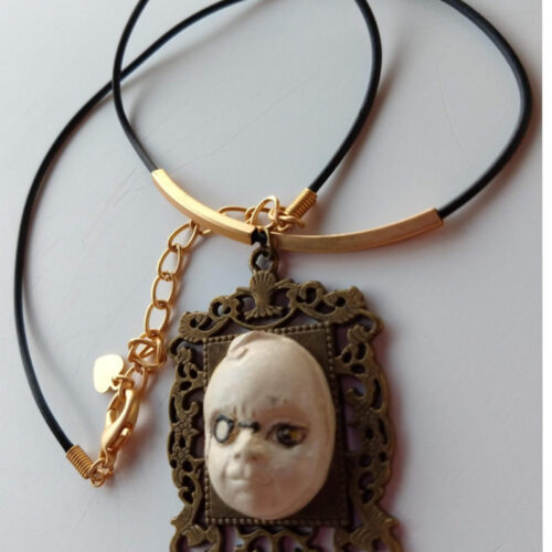 pendant with a face with a monocle by ursula aavasalu tigukass